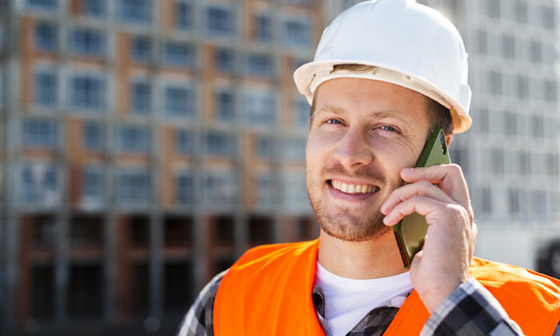 A construction foreman speaks by phone with a customer.