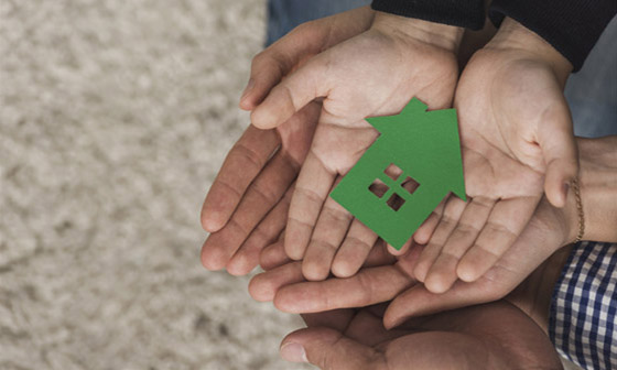 A father and child hold out their hands, they are holding a green model of a house.