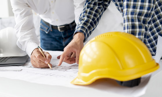 Two workers look over construction plans, their hardhats sit on the table nearby. When you need a reliable contractor, you can depend on Hammer It because your neighbors do, too.
