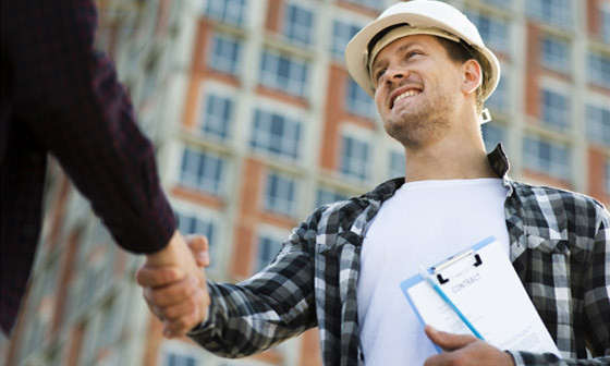 A construction foreman shakes hands with a customer.